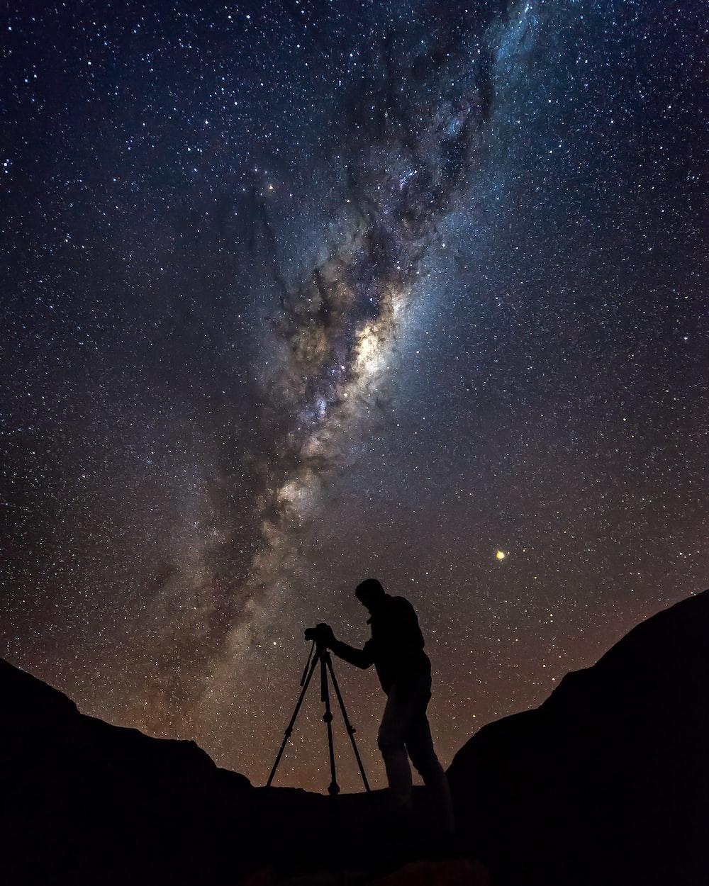 silhouette photo of man under Aurora phenomenon