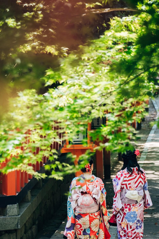 two geisha walking on concrete walkway