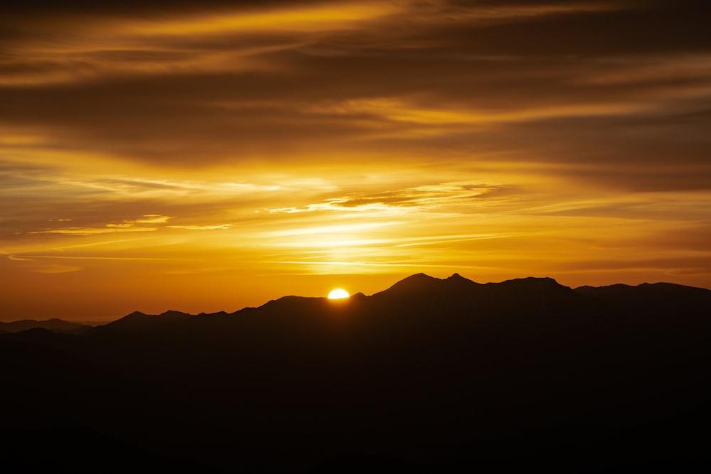 sun setting behind mountains