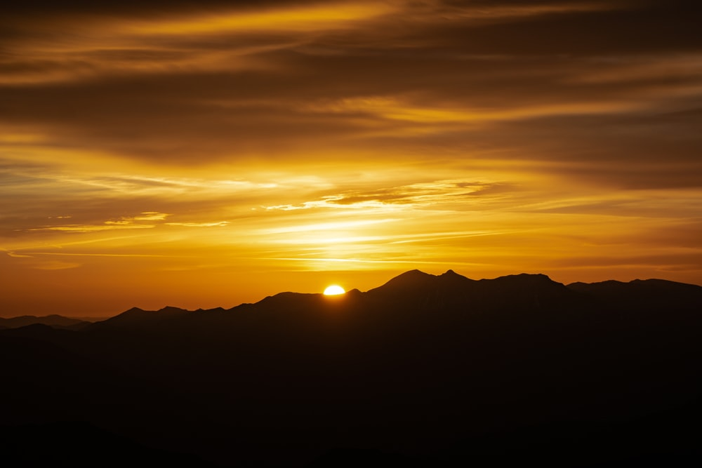sun setting behind mountains