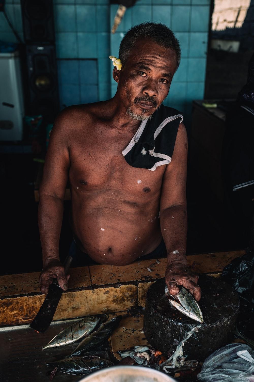 man holding machete and fish