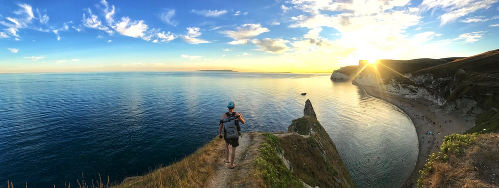 panoramic photography of man walking on cliff
