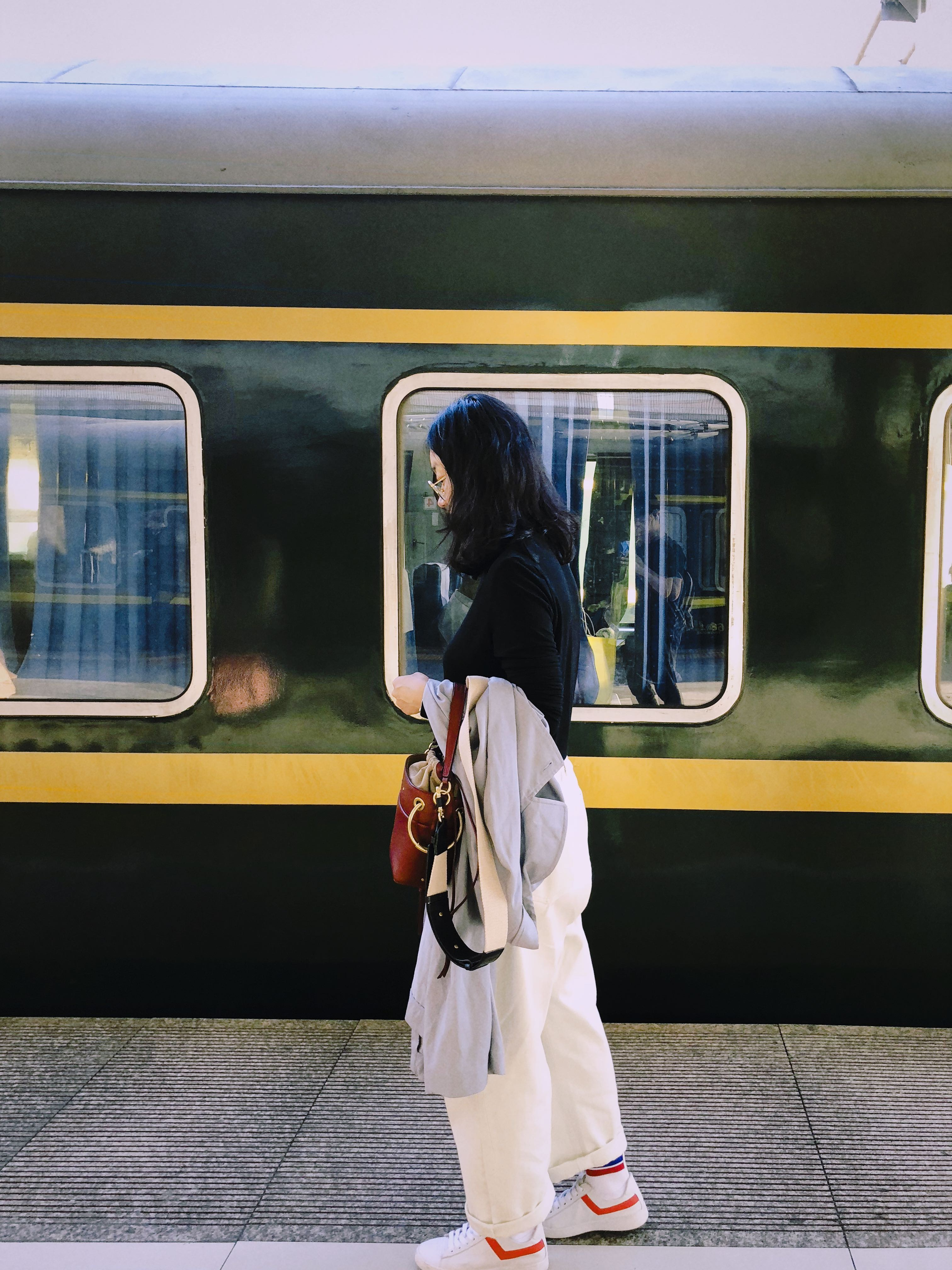 woman standing holding red bag near train