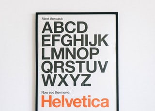 wall mounted Helvetica alphabet poster above sofa