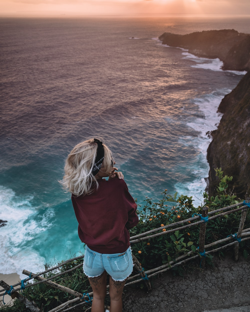 woman standing on cliff near body of water