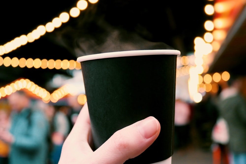 person holding black cup