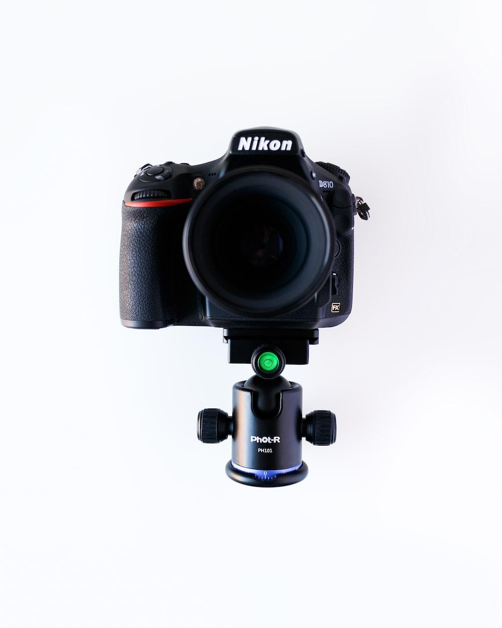 black Nikon DSLR camera with lens