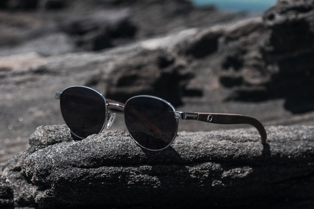 black lens sunglasses on rock