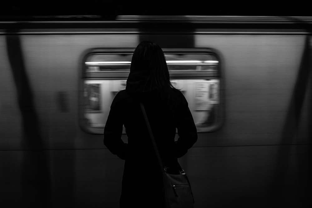 grayscale photography of woman standing near running train