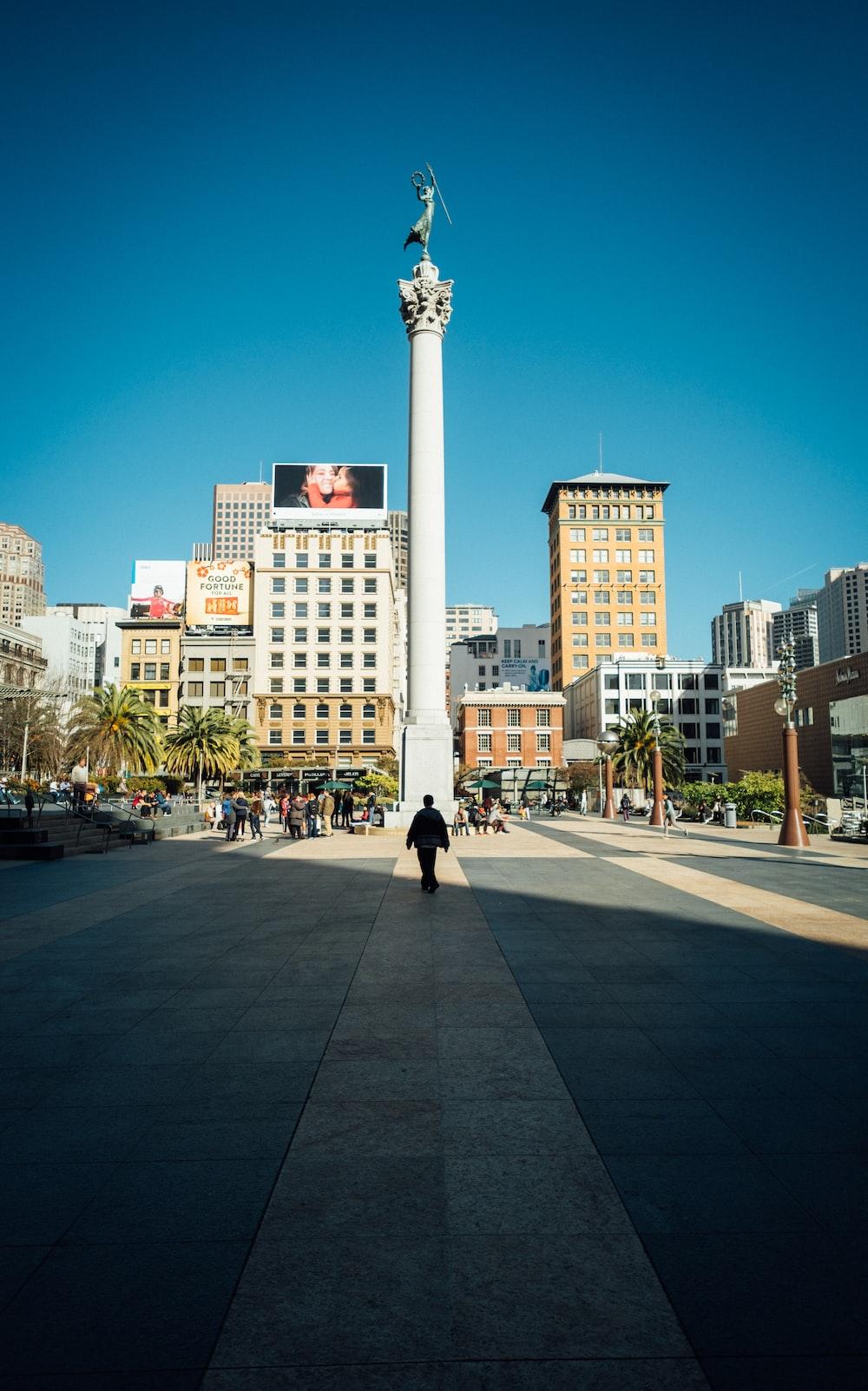 man walking infront of white tower