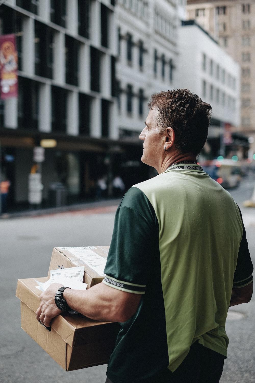 man carrying cardboard boxes during daytime