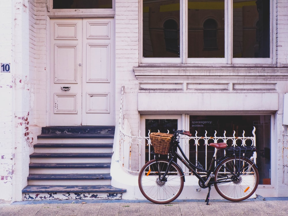 brown bike parked beside house