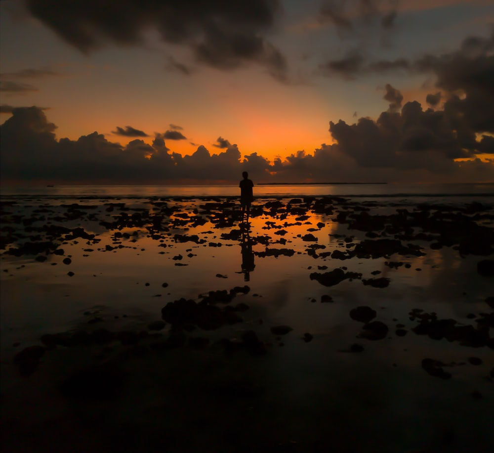 silhouette of person standing on rocks on sea