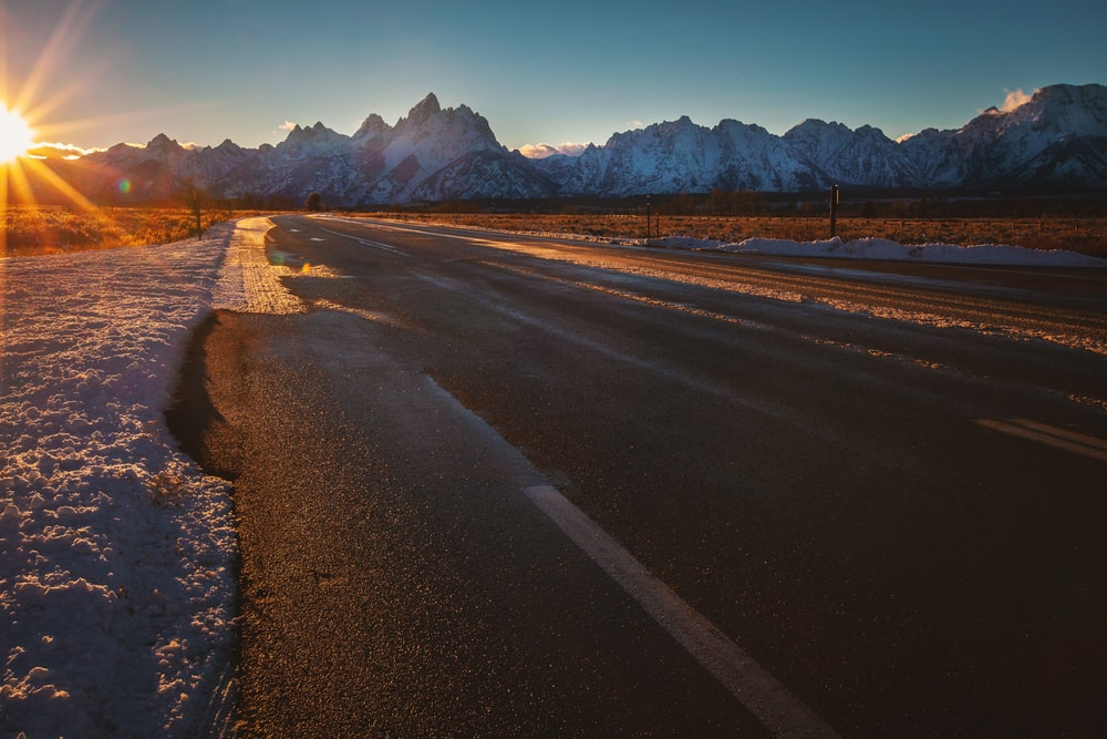 empty road near ice-capped mountains during golden hour
