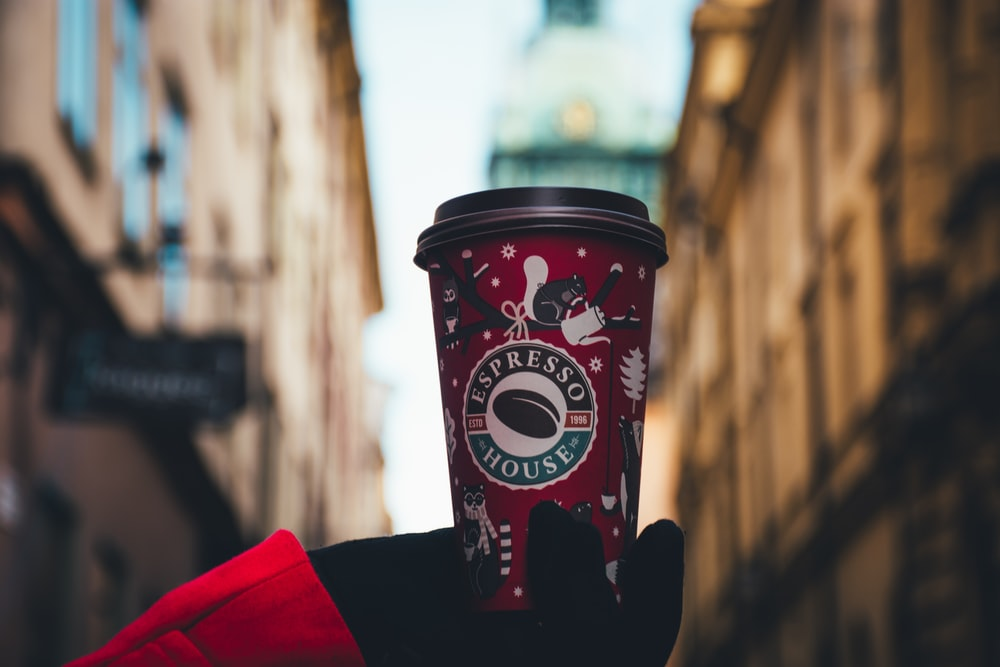 person holding red tumbler