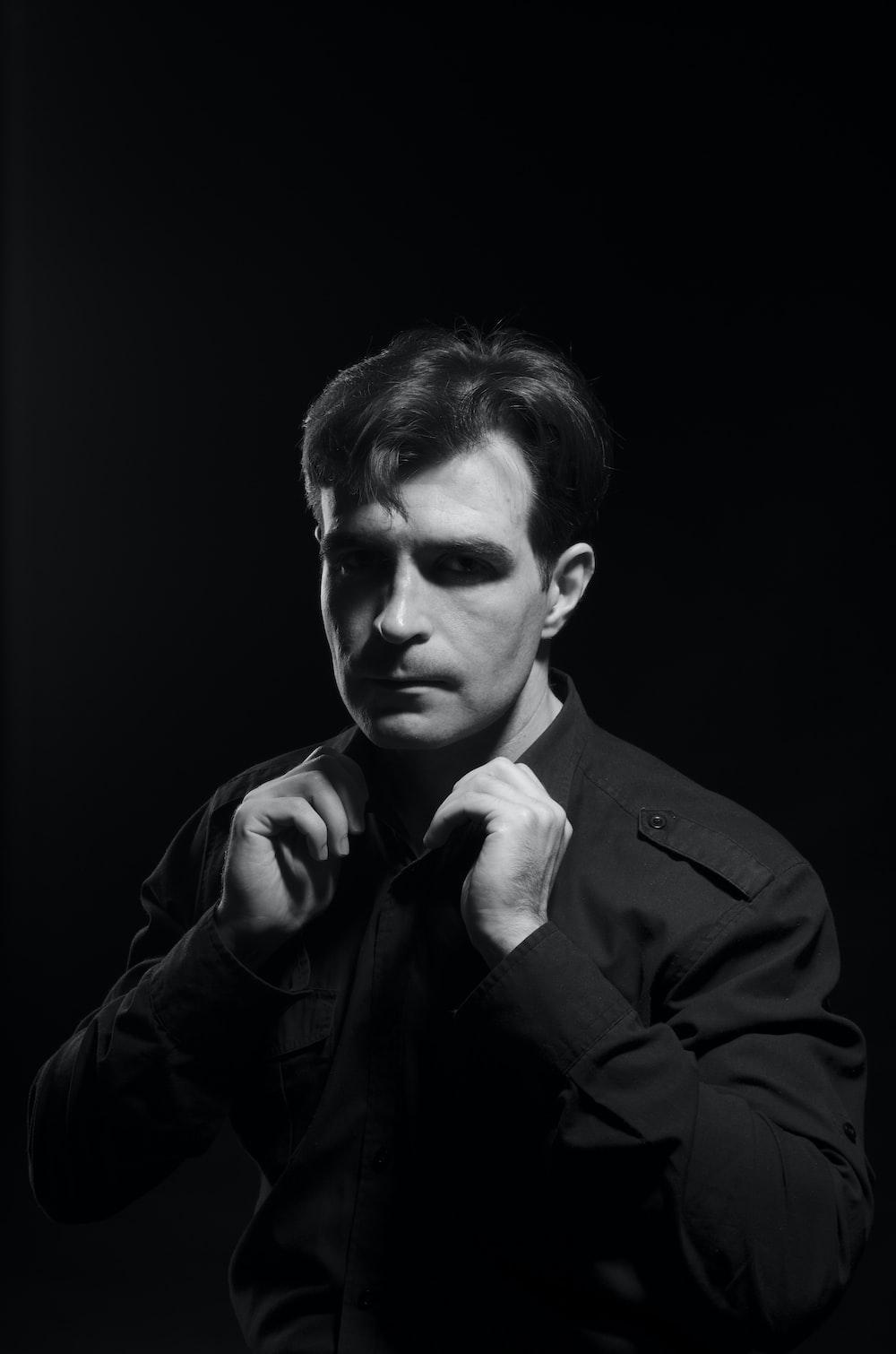 man wearing dress shirt while holding his collar