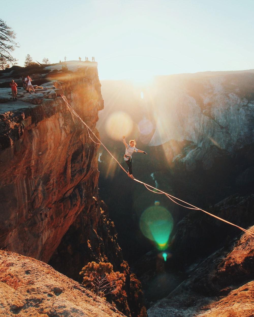 man walking on string hanging from rock mountains