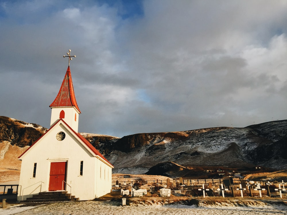 white and red cathedral near mountain