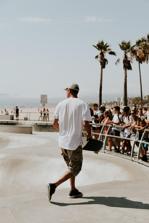 man in white shirt holding skateboard