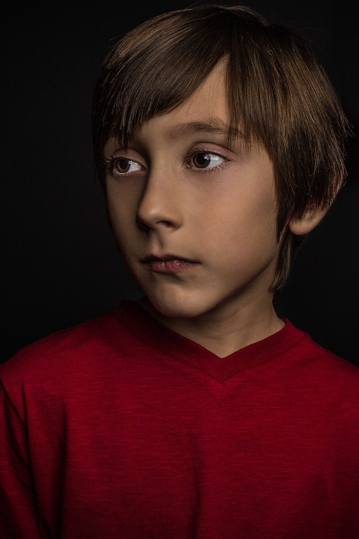 boy wearing red crew-neck shirt