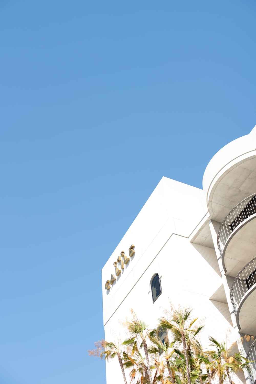 low angle photo of white painted building under clear blue sky