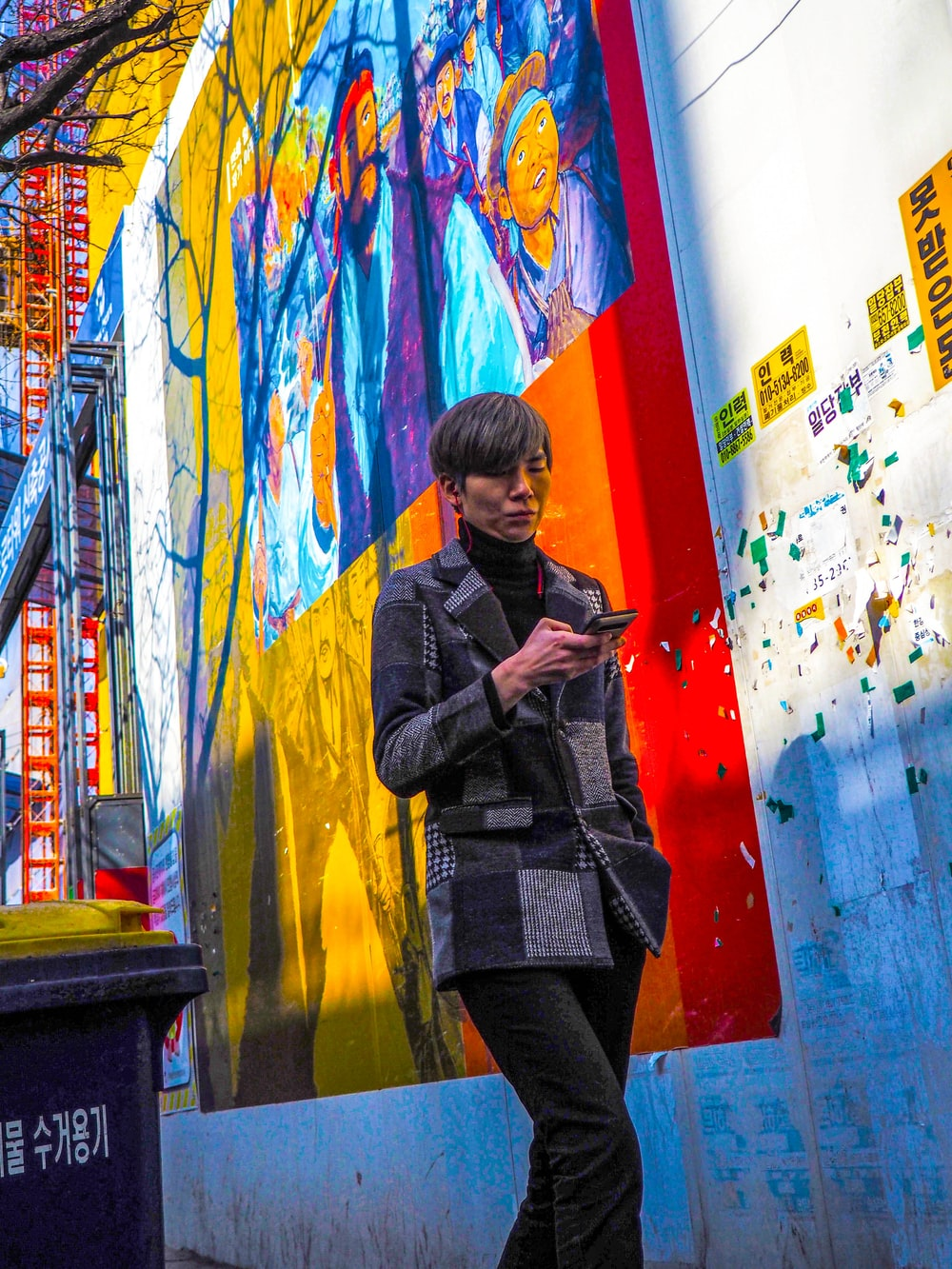 person in gray coat holding smartphone while walking near graffiti wall