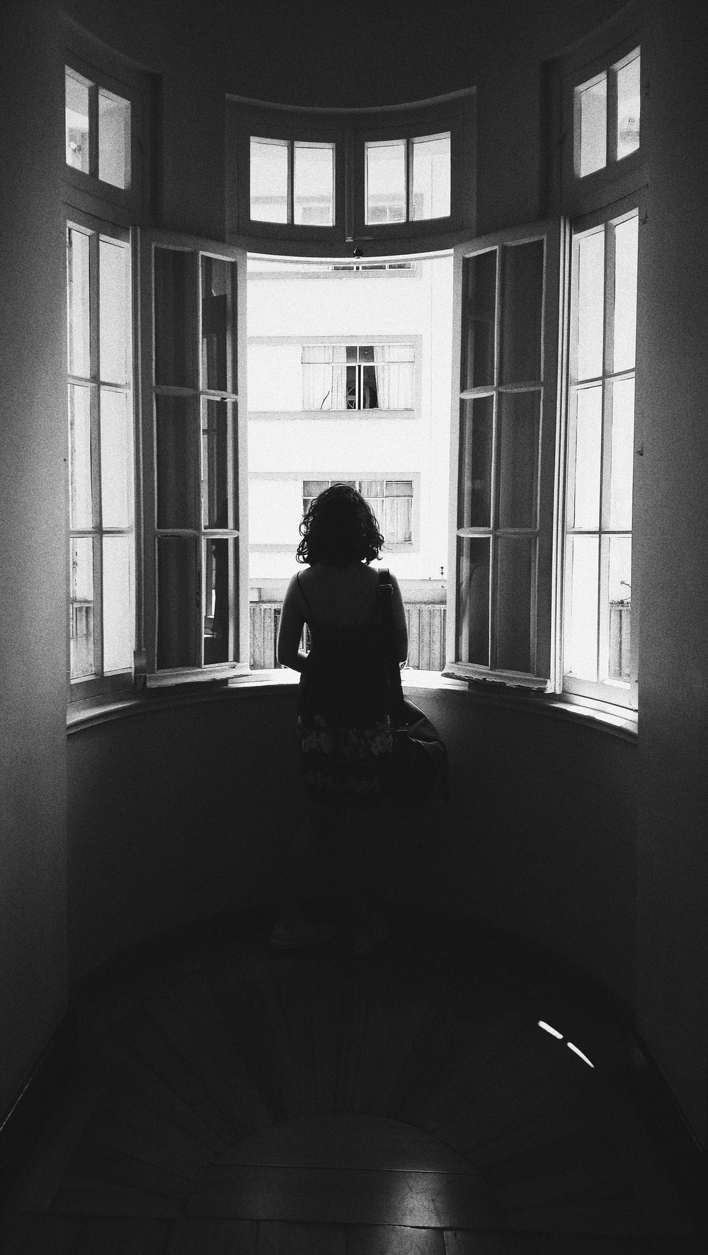 grayscale photo of woman standing in front of window