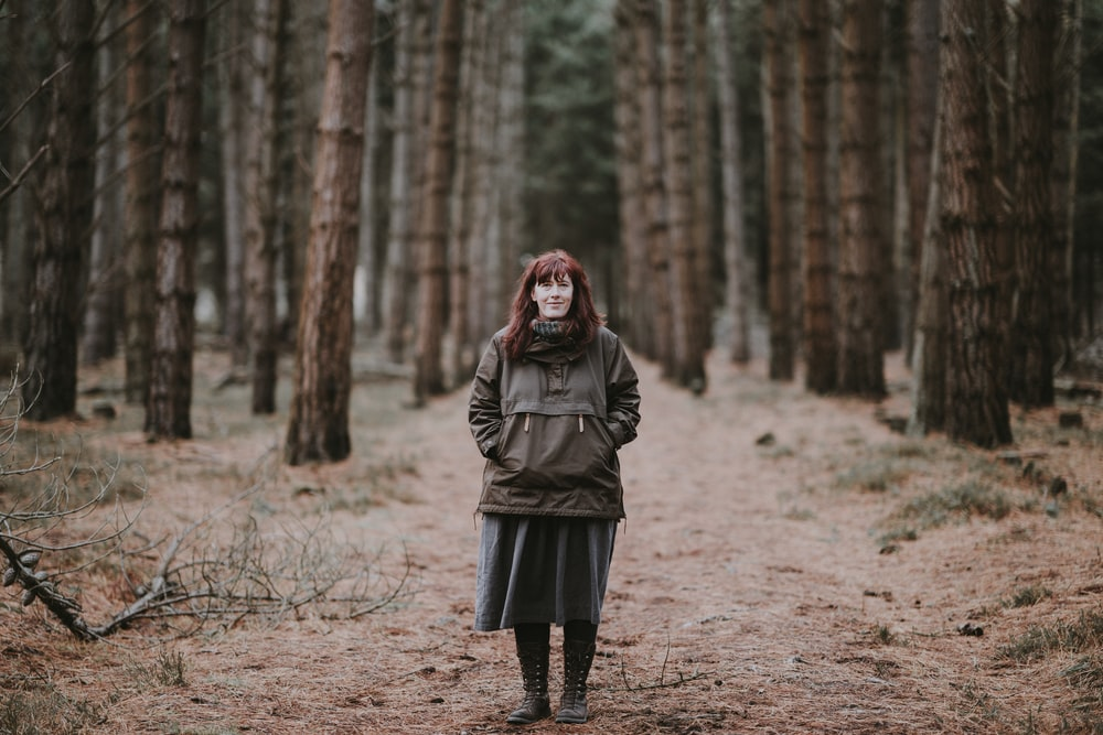 woman in green jacket standing in the middle of dirt trail at the woods