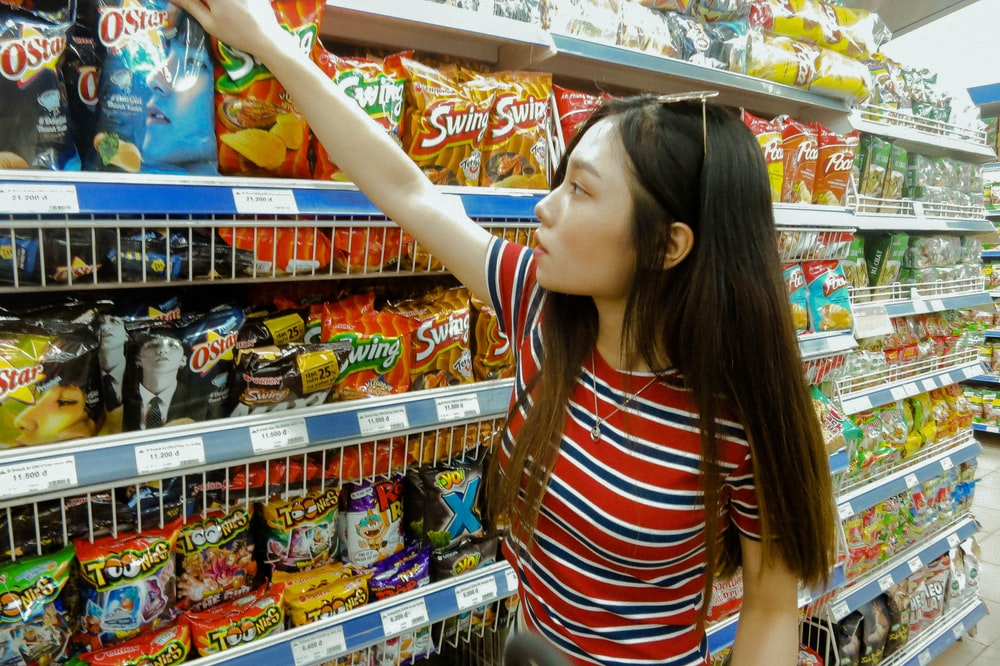 woman standing while grabbing plastic pack