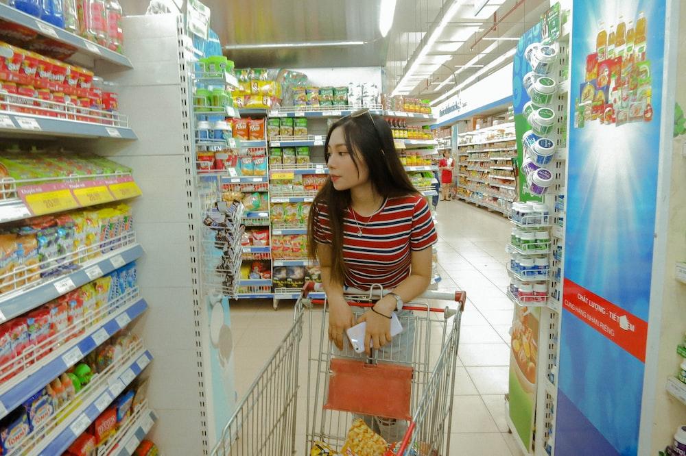 woman standing between gondola shelves