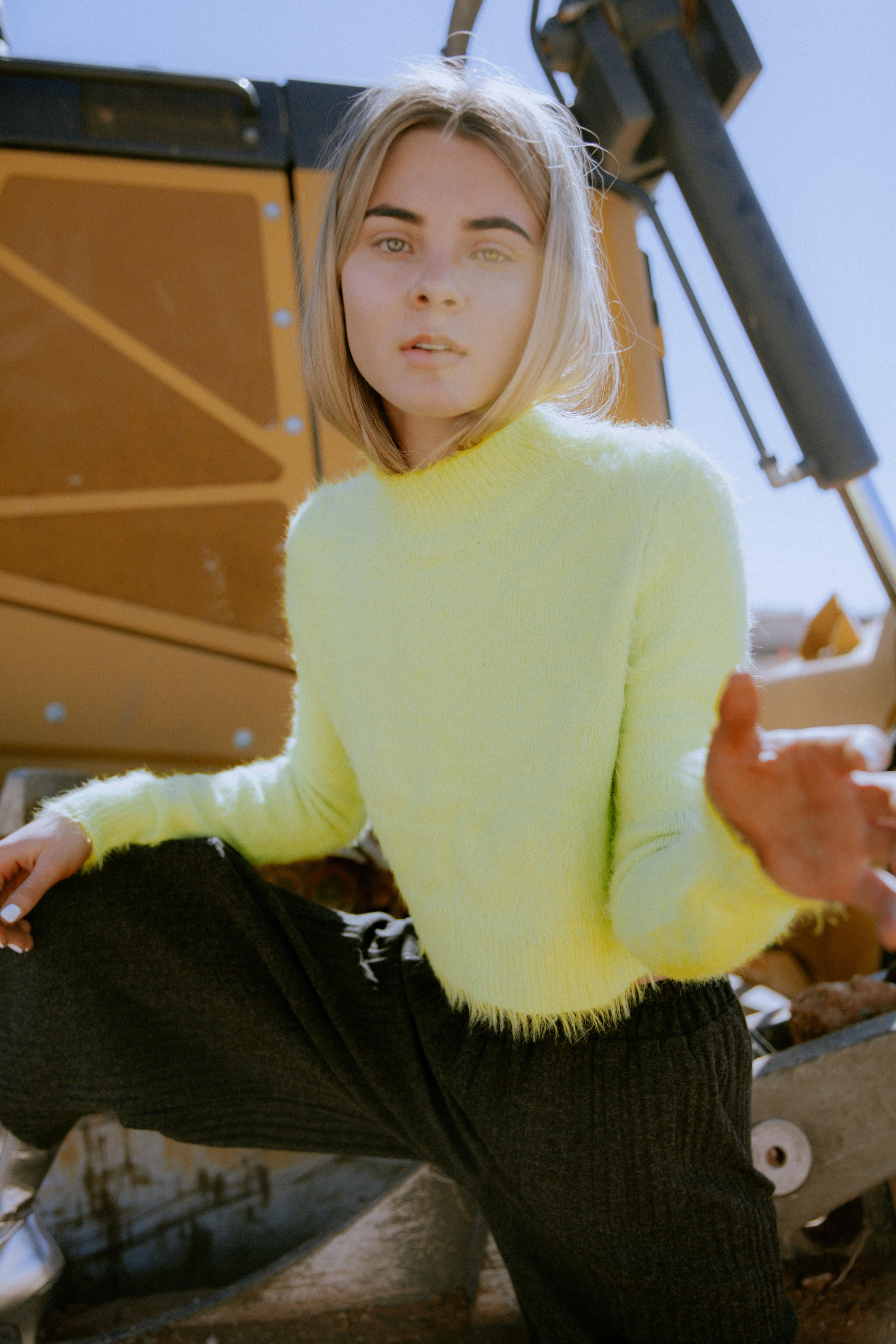 woman standing on yellow heavy equipment