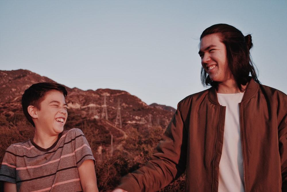 man in jacket beside boy in t-shirt smiling