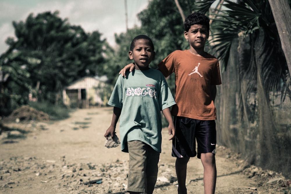 two boy walking on footpath