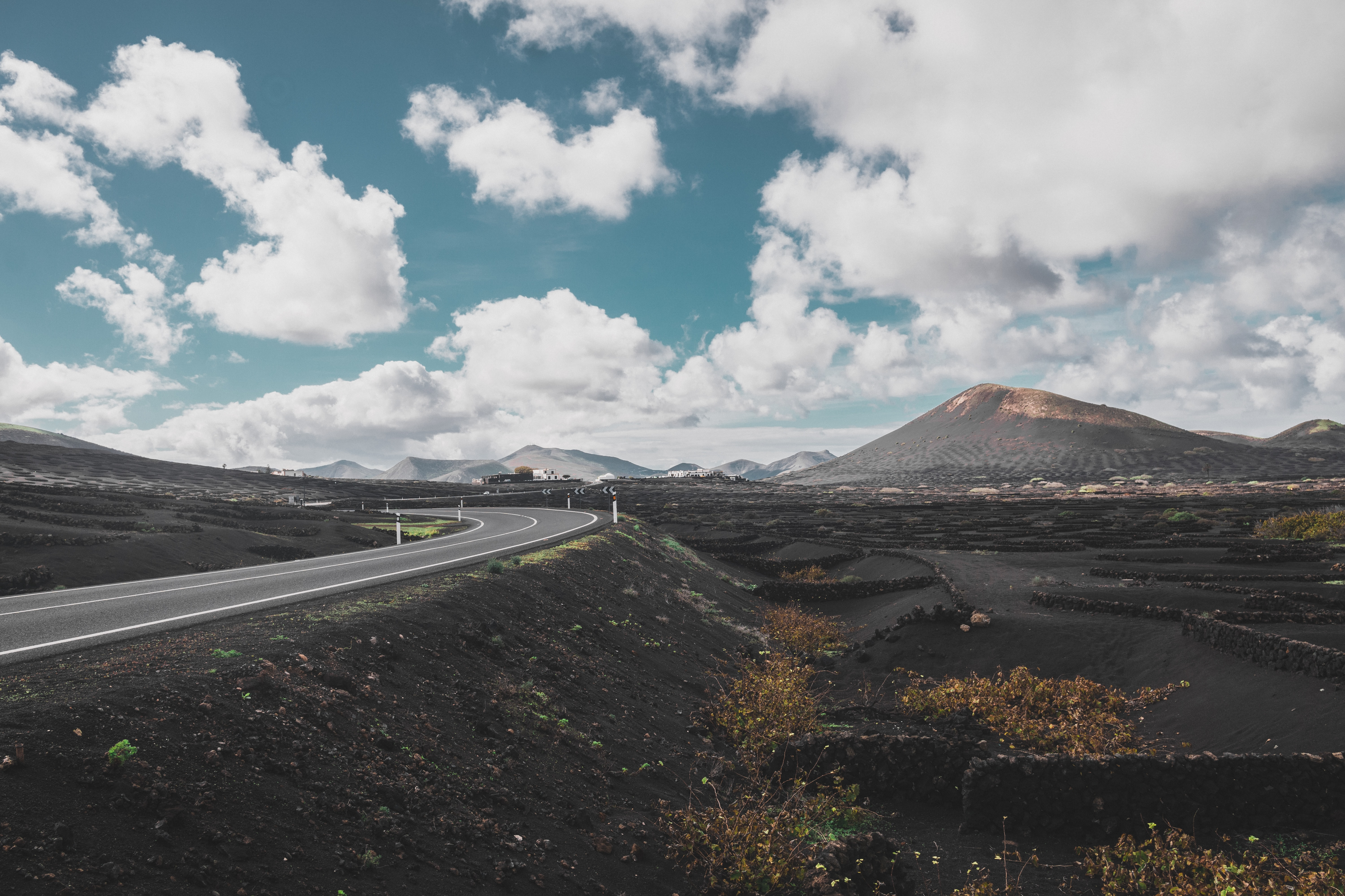 road far from mountain under white clouds