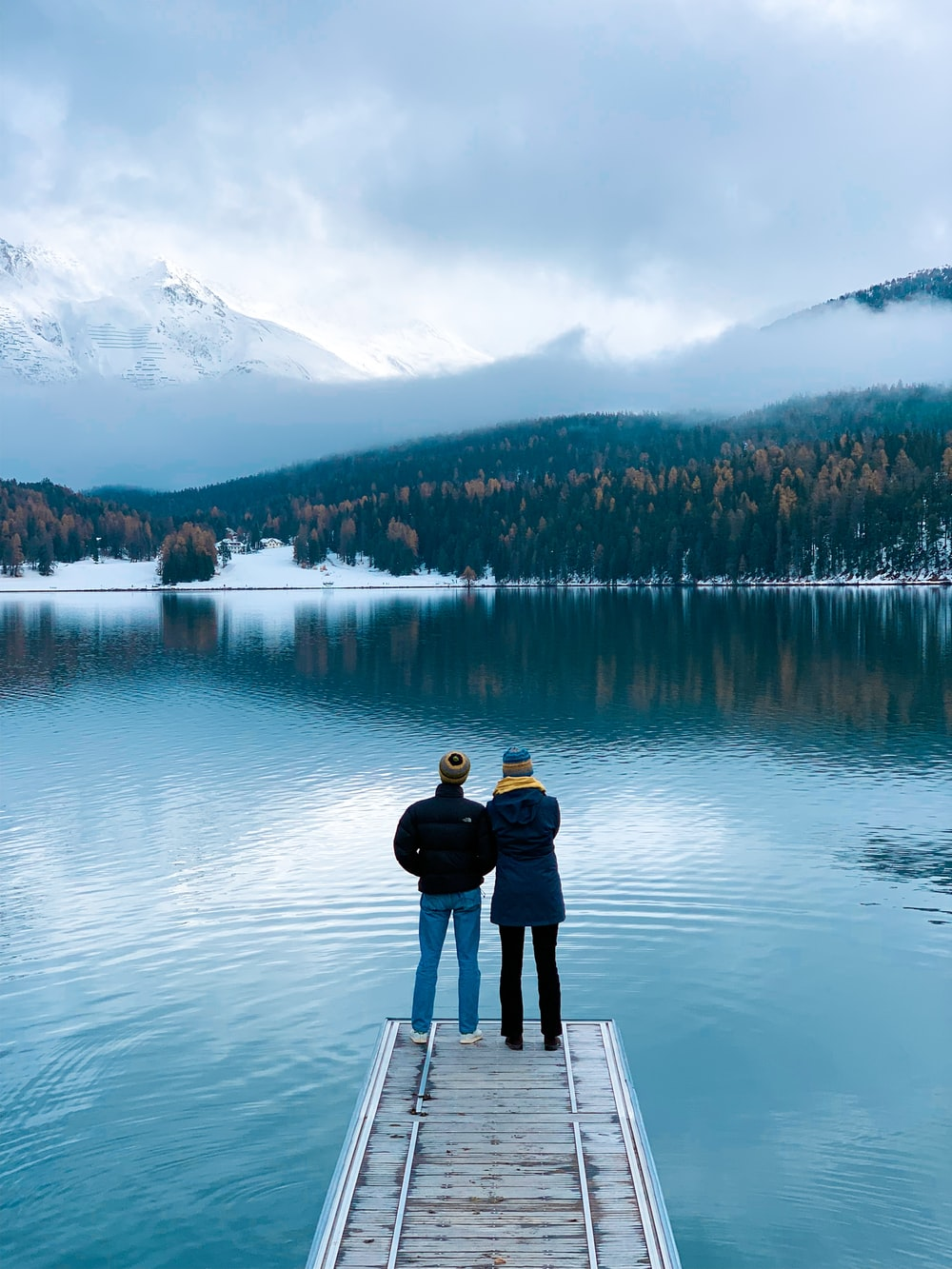 two persons standing on dock during daytime