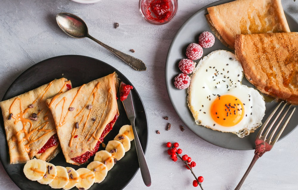 fried egg, bread and raspberry on plate