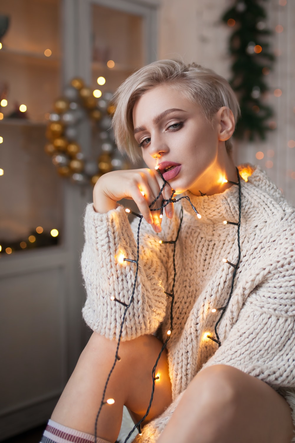 woman in beige sweater with orange string lights on her body