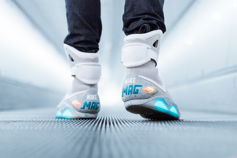 person wearing grey Nike Mag sneakers