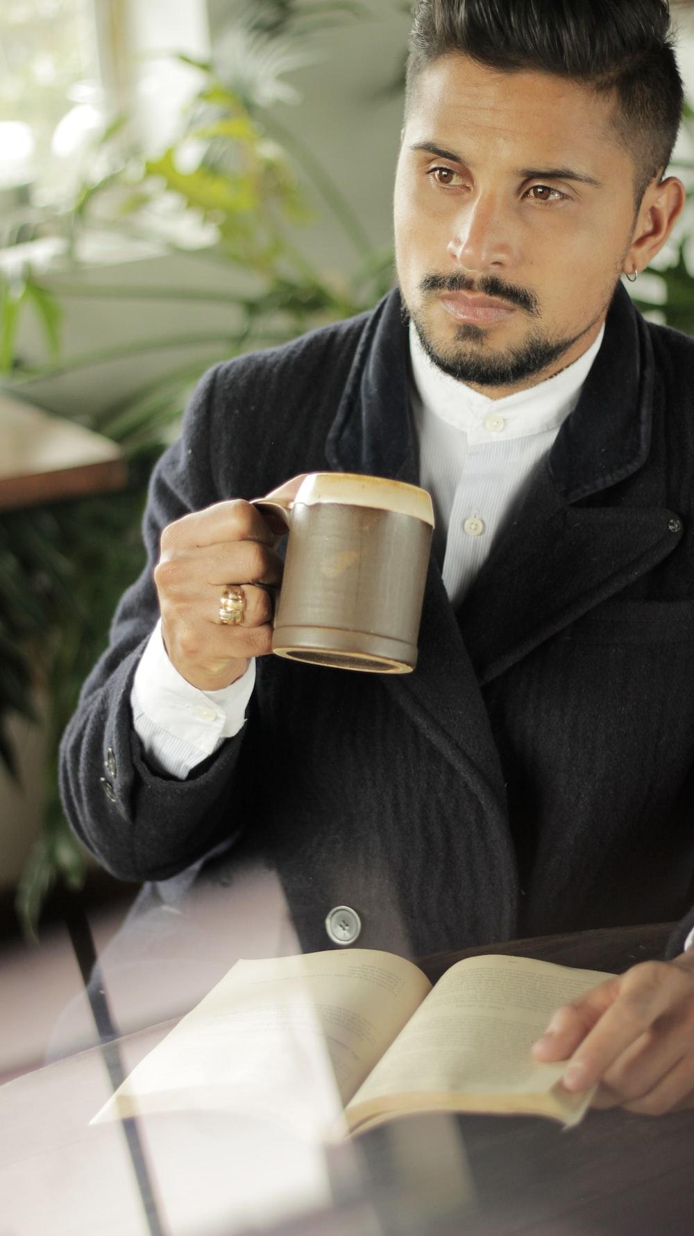 man holding brown mug
