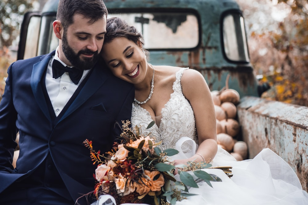 man and woman wearing wedding dress while sitting on truck