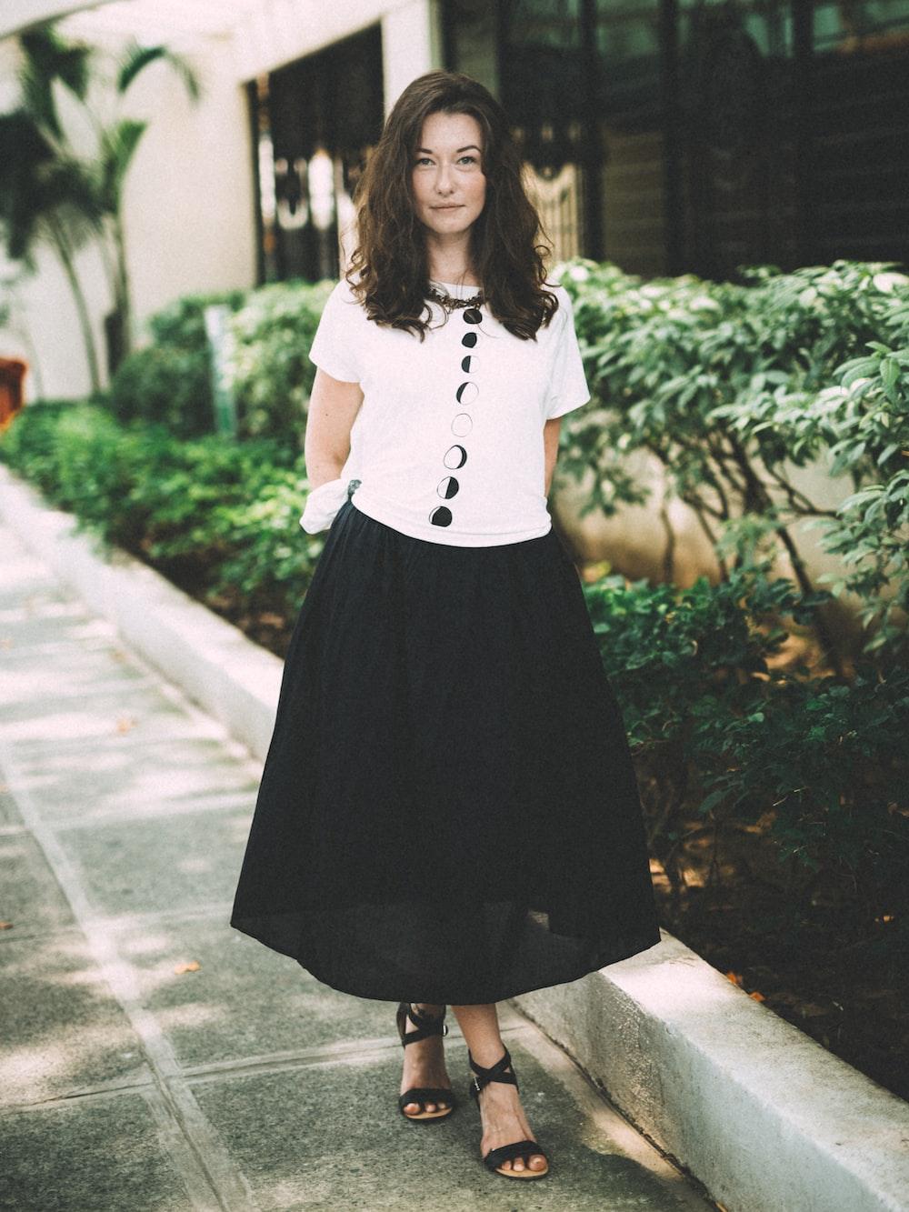 woman wearing black skirt standing beside plants