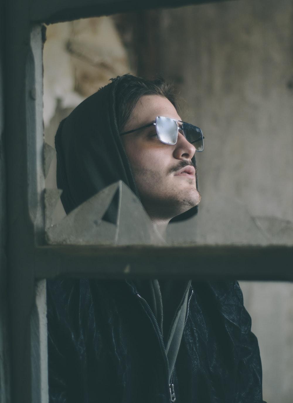 man wearing black zip-up hoodie and sunglasses
