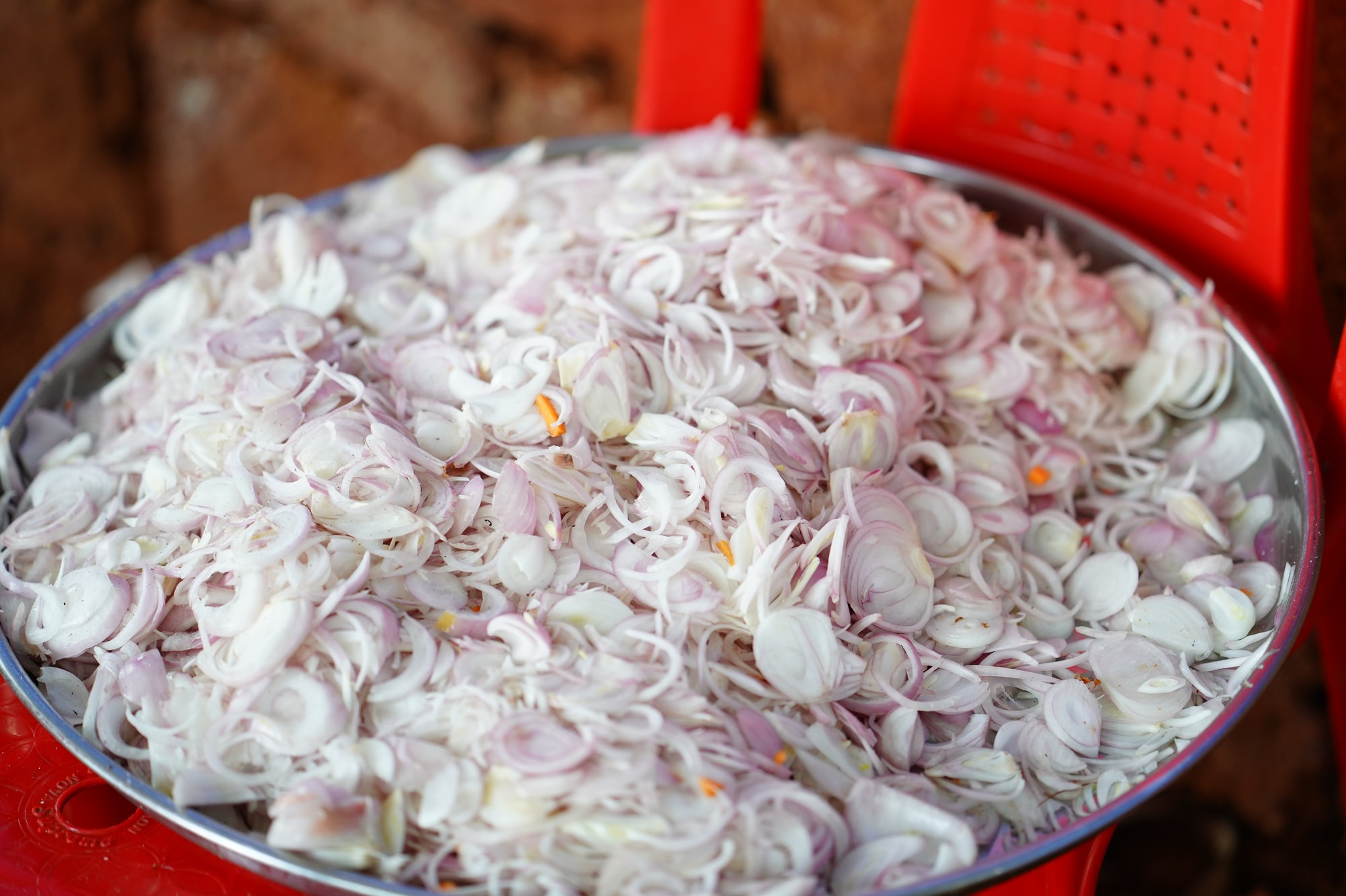 An stainless steel plate full of sliced onions, placed on a red plastic chair.