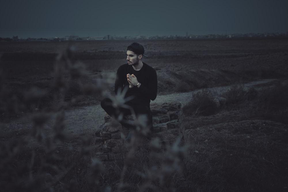 man sitting near the grass photography