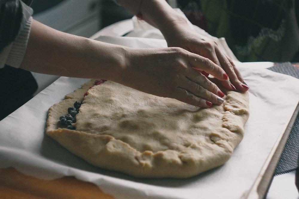 woman making dough on white textile