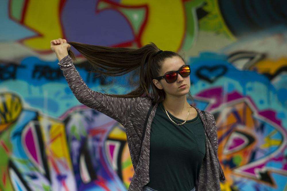 woman holding her hair standing near graffiti wall