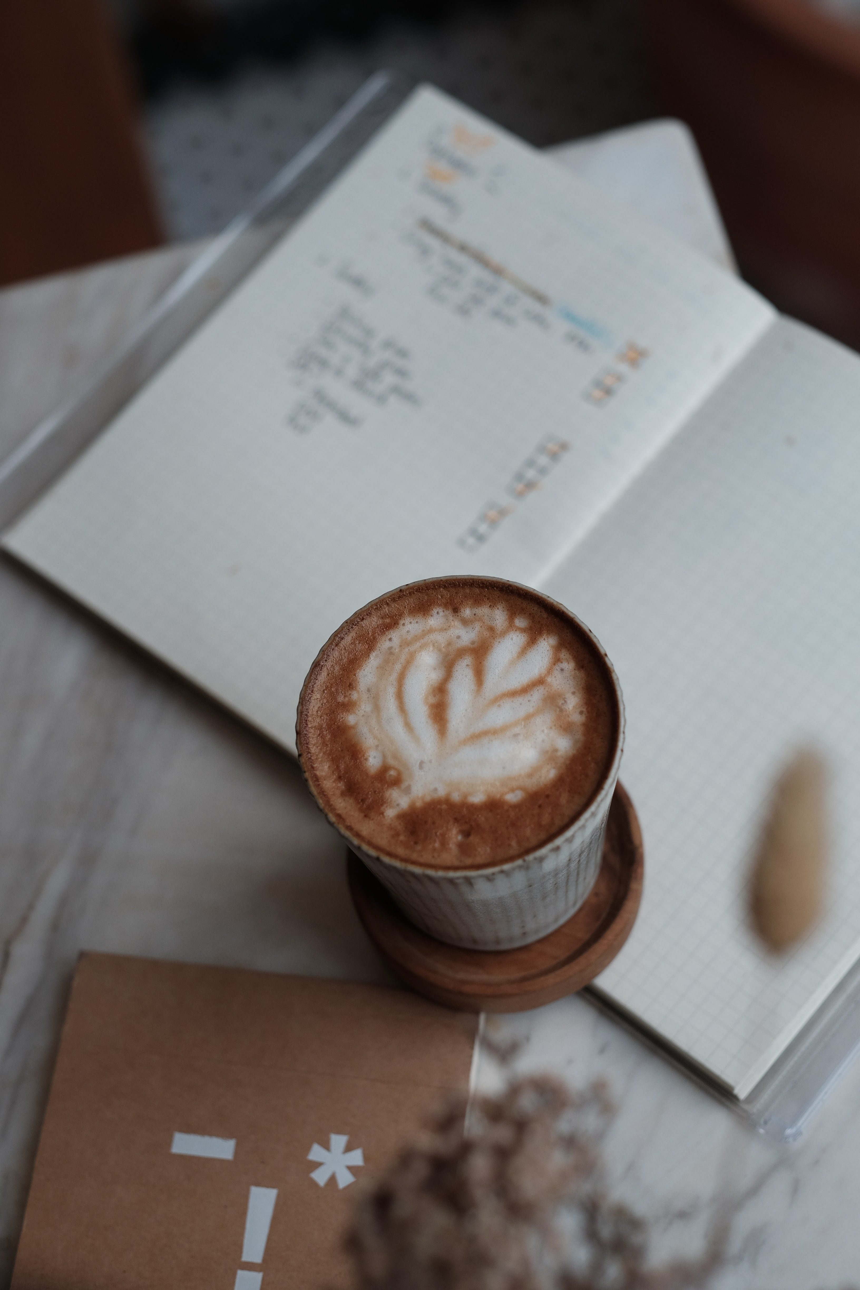 cappuccino in cup beside books