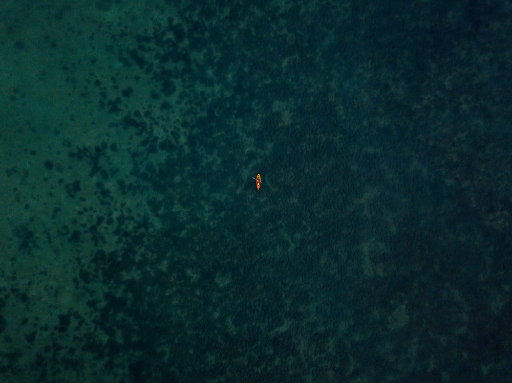 aerial photograph of brown boat on body of water