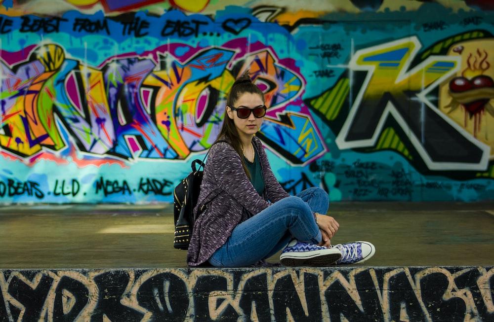 woman sitting on stage beside graffiti