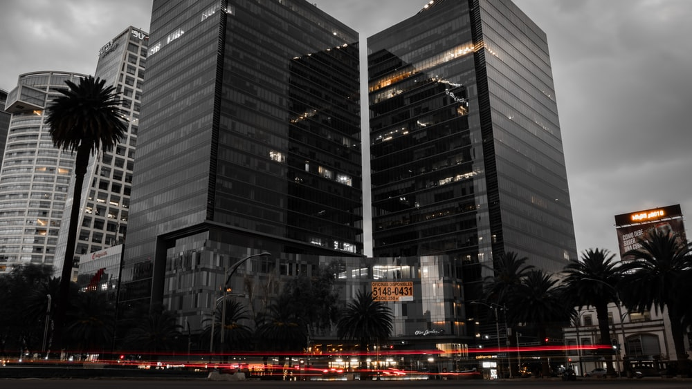 grayscale photo of two glass buildings near road